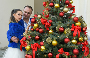 The bride and groom near the Christmas tree