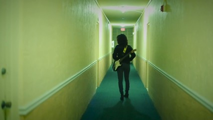 Female walking down hallway with Electric Guitar on her back