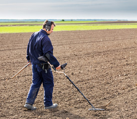 Man searching for treasure with metal detector