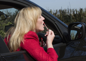 Female motorist applying lip gloss using driving mirror