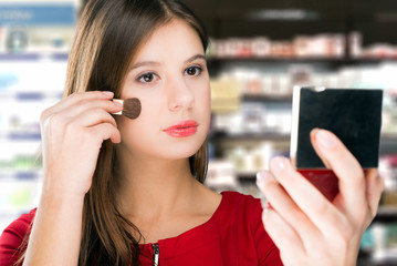 Young woman chooses make up in cosmetics shop.