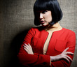 Stylish fashion girl in red suit and beret, posing at studio ove