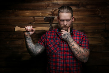 Criminal guy with axe on wood background
