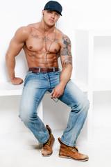 Muscular guy in blue jeans posing