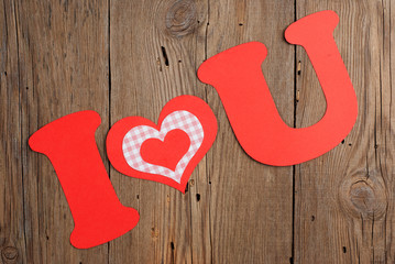 Phrase I LOVE YOU on old wooden background