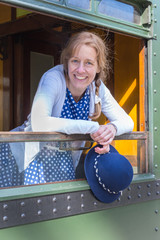 Woman in old-fashioned clothes holding hat in train window