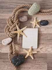 paper, rope, starfish, sea stones on the old wooden background