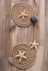 rope, starfish, sea stones on the old wooden background