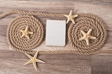 paper, rope, starfish on the old wooden background