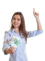 Frau mit braunen Haaren und Geld zeigt nach oben