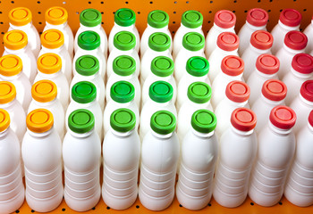 dairy products bottles with bright covers onshelf in shop..