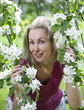 young woman standing near blossoming apple tree...