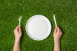 Hands holding fork and knife with plate on grass - 81631528