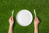 Hands holding fork and knife with plate on grass