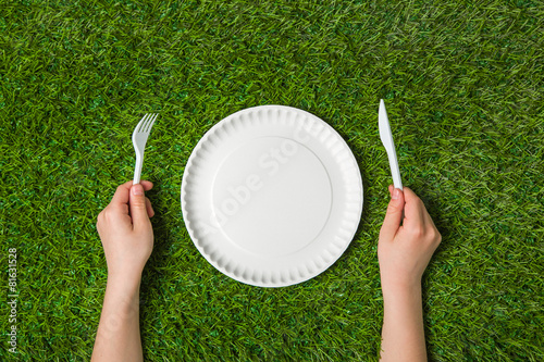 Fotobehang Picknick Hands holding fork and knife with plate on grass