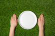Hands lying near empty paper plate on green grass - 81631737
