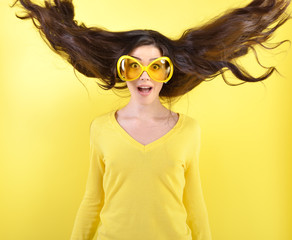 Joyful excited surprised young woman with flying hair and big fu
