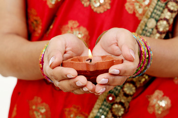 Hands holding a traditional Indian oil lamp