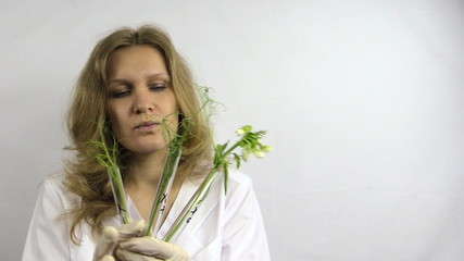 Scientist woman research flasks with genetically modified plants