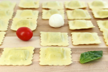 Ravioli arranged in a row with tomato, bocconcini and basil