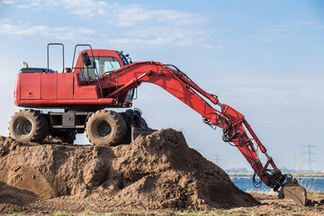 Red excavator on a pile of sand