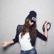 girl in  black cap and earphones in hands