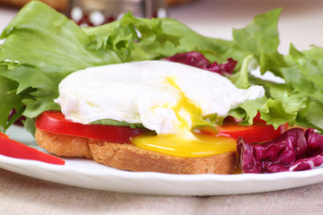 Poached egg with toast and salad, close-up