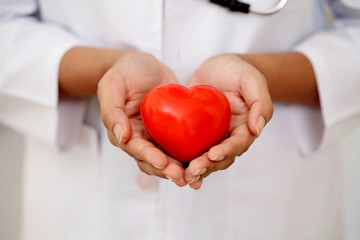 Female doctor holding a beautiful red heart shape