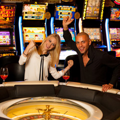 Young couple playing roulette in casino betting and winning