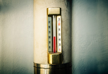 Old vintage thermometer in house heating system.