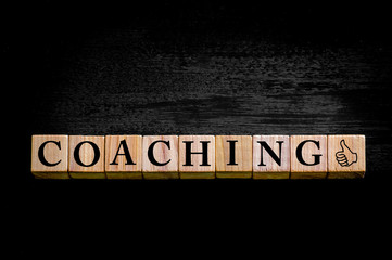 Word COACHING isolated on black background