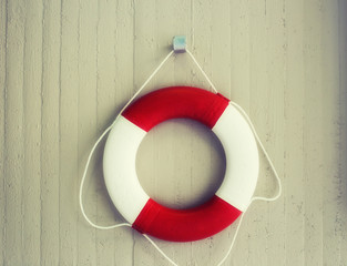 Red life buoy hanging on a wall. Help and support concept