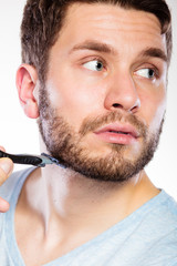 Young man with beard holding razor blade