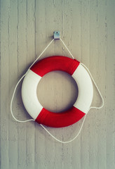 Red life buoy hanging on a wall. Help and safety concept.