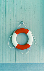 Red life buoy hanging on a wall. Help and support concept.