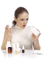 Beautiful surprised young woman looking into the pill bottle
