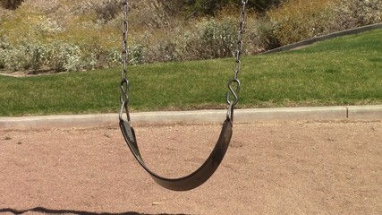 An empty swing swinging in a playground in Mesa, Arizona