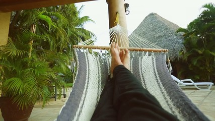 Person's legs resting on a Hammock on a beautiful setting