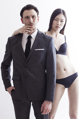 Businessman portrait with chinese model wearing basic lingerie