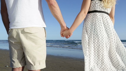 Holding hands - romantic couple on beach
