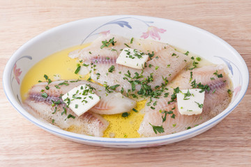 Fresh raw fish with butter, olive oil, lemon juice, herbs and