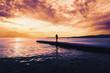 Woman walking on pier at sunset
