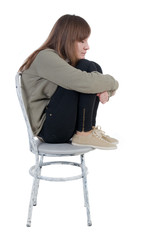 Lonely, closed woman sitting on chair.