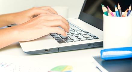 closeup hand typing on keyboard laptop business work
