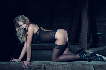 Sexy blonde woman kneeling with whip in barn