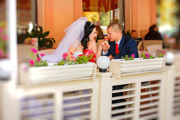 Bride and groom drinking coffee at an outdoor cafe
