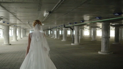 A young bride  wandering alone about the parking