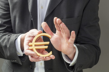 businessman holding Euro symbol in his hands