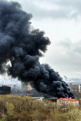 Column of black smoke rising above fireplace in the city