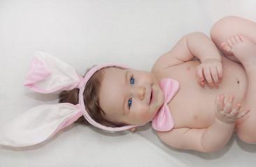 portrait of cute little happy baby boy with rabbit's ears lying